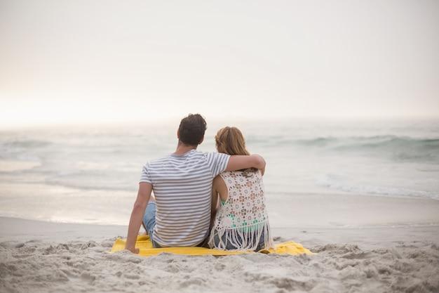 Achteraanzicht van paar zittend op het strand