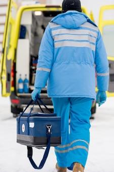Achteraanzicht van paramedicus in blauwe werkkleding en medische handschoenen met een ehbo-kit terwijl hij naar de ambulanceauto gaat