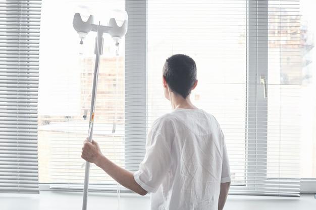 Achteraanzicht van patiënt met druppelaar die voor het raam op de ziekenhuisafdeling staat