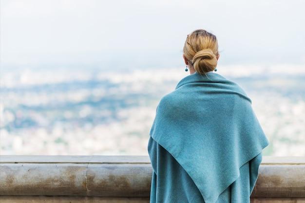 Achteraanzicht van peinzende eenzame jonge vrouw in blauwe kleren op zoek in de verte met hoop.