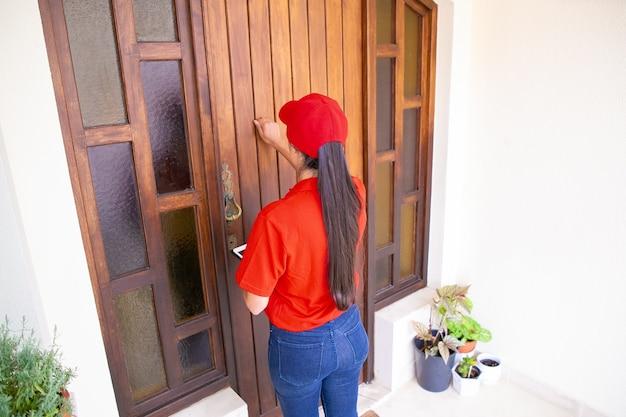 Achteraanzicht van postbode kloppen op de deur en tablet te houden. brunette vrouwelijke koerier in rood uniform staande voor deur en bestelling leveren aan klant. bezorgservice en postconcept