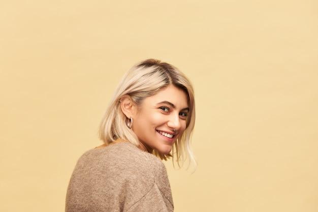Achteraanzicht van prachtige positieve jonge europese vrouw die warme, gezellige trui draagt die het hoofd ronddraait en met een stralende, gelukkige glimlach, in goed humeur is, speelse gezichtsuitdrukking heeft