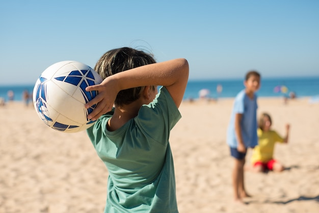 Achteraanzicht van preteen jongen die bal op het strand gooit