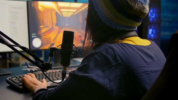 Achteraanzicht van pro-gamervrouw die first-person videogames speelt met rgb-toetsenbord in thuisstudio