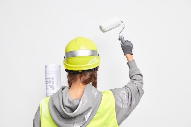 Achteraanzicht van professionele architect bezig met ontwerpontwikkeling houdt architecturale blauwdruk verven muren met roller draagt beschermende helm uniform geïsoleerd op witte muur ontwikkelt nieuwe ideeën