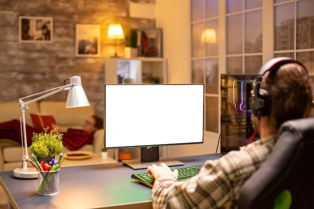 Achteraanzicht van professionele gamer die 's avonds laat in de woonkamer naar een computer kijkt met een geïsoleerd mock-upscherm