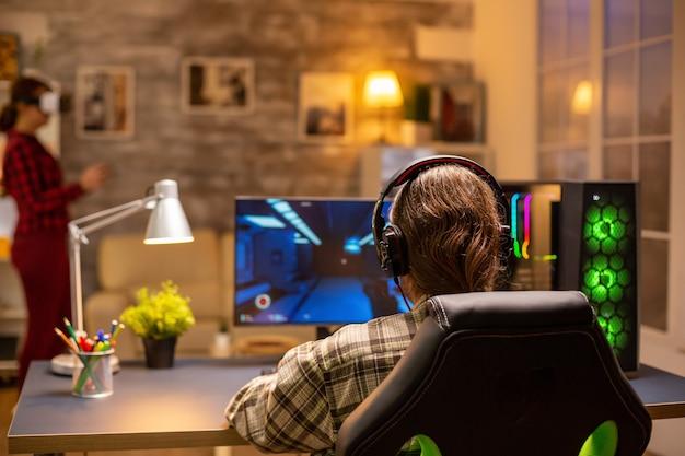 Achteraanzicht van professionele videogamer die 's avonds laat in de woonkamer op een krachtige pc speelt.