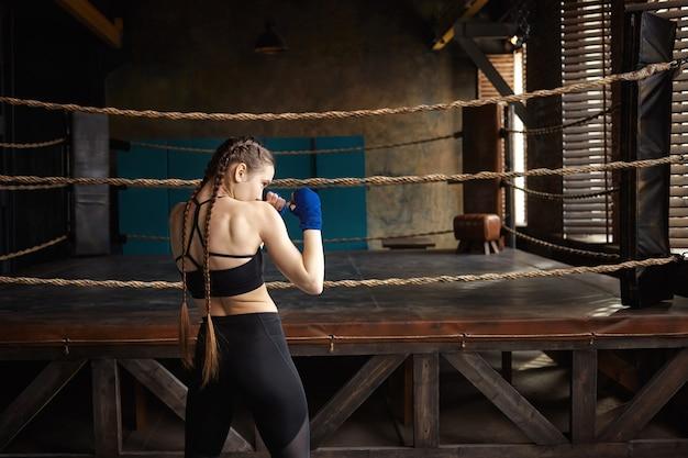 Achteraanzicht van professionele vrouwelijke bokser met twee vlechten permanent in lege sportschool met boksring op achtergrond, alleen training