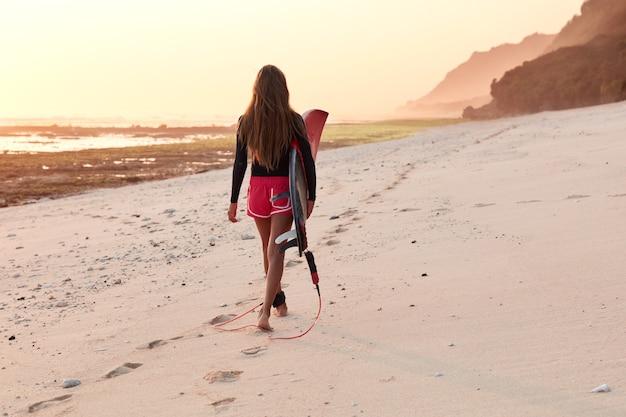Achteraanzicht van professionele vrouwelijke surfer in duikpak wandelingen over kustlijn in de buurt van de oceaan