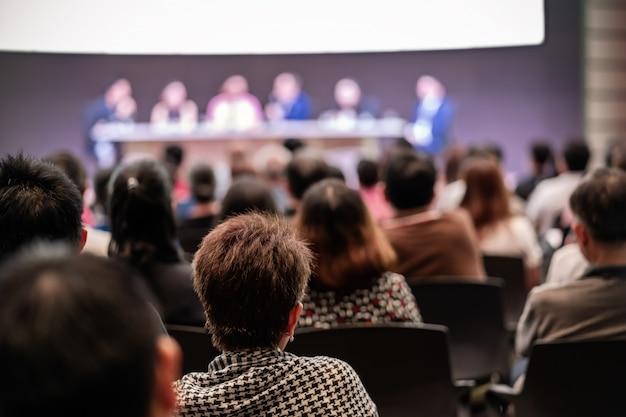Achteraanzicht van publiek in de conferentiezaal of seminarvergadering met sprekers