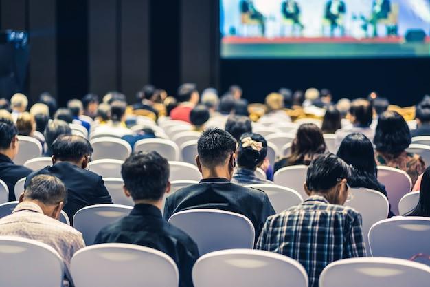 Achteraanzicht van publiek luisteren sprekers op het podium in de conferentiezaal of seminar vergadering, zakelijke en onderwijs over investeringsconcept