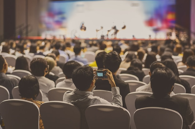 Achteraanzicht van publiek luisteren sprekers op het podium in vergaderzaal voor seminars