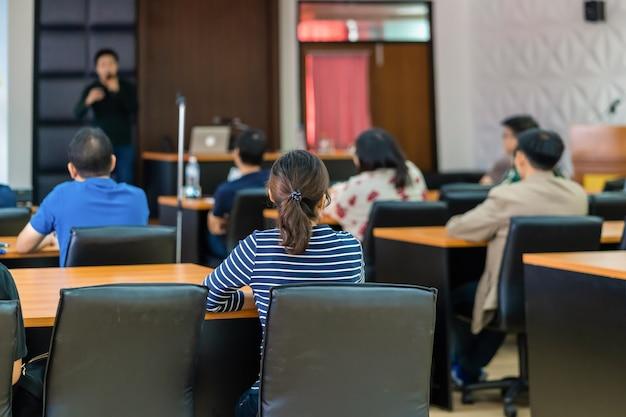 Achteraanzicht van publiek luisteren sprekers op het podium