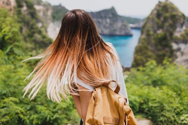 Achteraanzicht van reizende vrouw op kliffen en tropisch strand. vrijheid en avontuur concept.