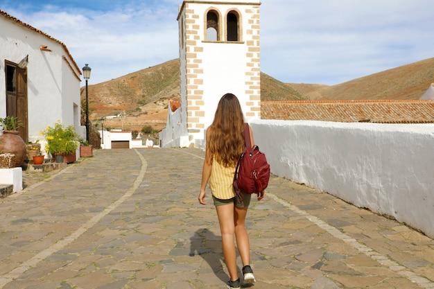 Achteraanzicht van reiziger meisje wandelen in kleine koloniale stad betancuria, canarische eilanden, spanje