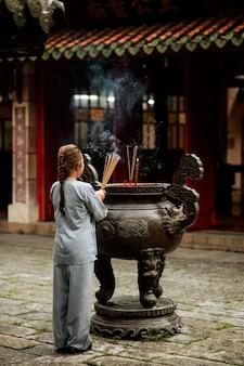 Achteraanzicht van religieuze vrouw met wierook branden in de tempel