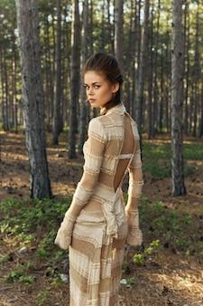 Achteraanzicht van romantische mensen in jurk in de natuur in het bos en naaldbomen