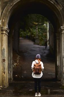 Achteraanzicht van roodharige vrouwelijke toerist die prachtige architecturale bouwplaatsen bewondert tijdens het wandelen in...