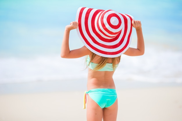 Achteraanzicht van schattig klein meisje in grote hoed op wit strand