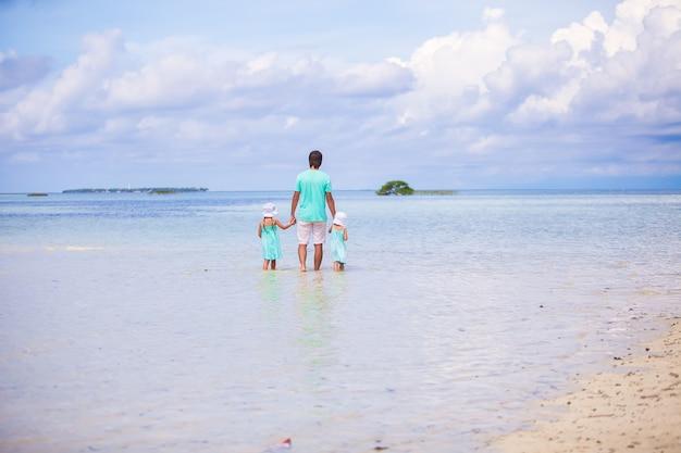 Achteraanzicht van schattige kleine meisjes en jonge vader lopen op exotisch eiland