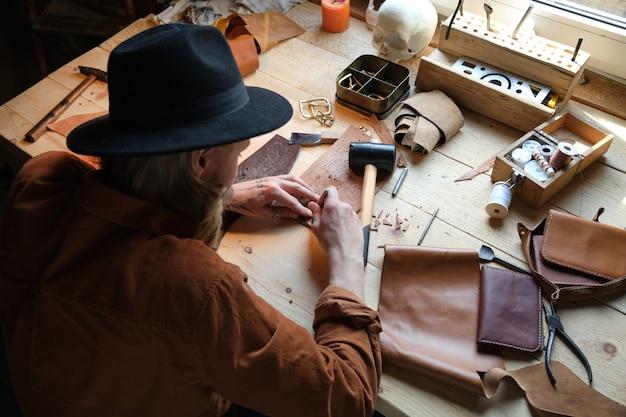 Achteraanzicht van schoenmaker in hoed zittend aan tafel met patronen en schoenen maken van leer in de werkplaats
