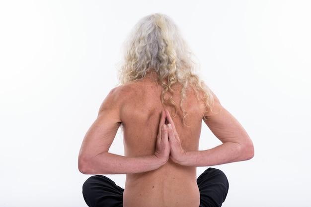 Achteraanzicht van senior bebaarde man doet yoga houdingen met beide handen