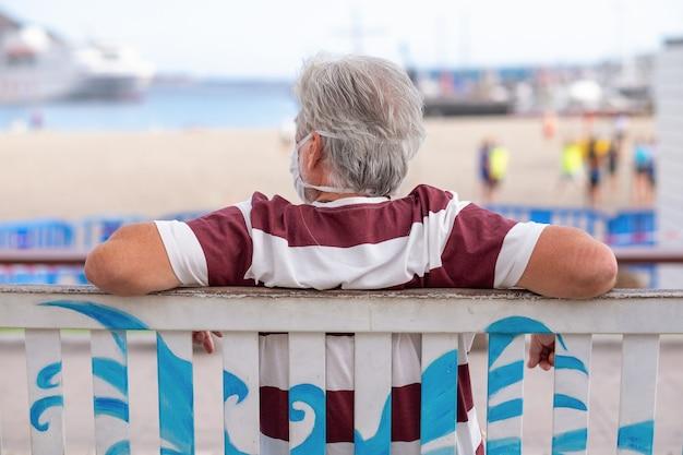 Achteraanzicht van senior man met medisch masker als gevolg van coronavirus zittend op een bankje kijkend naar het strand en de zee. vakantie en pandemie concept