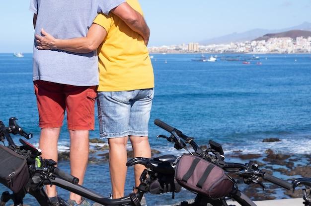 Achteraanzicht van senior paar knuffelen staande op de klif in zee-excursie met hun fietsen, horizon aan zee. actieve gepensioneerden die genieten van een gezonde levensstijl en vrijheid. zeegezicht en uitzicht op de bergen