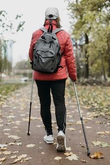 Achteraanzicht van senior vrouw buitenshuis met wandelstokken