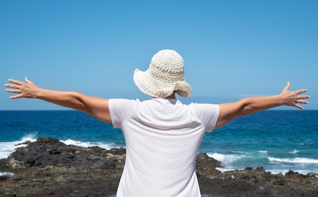 Achteraanzicht van senior vrouw met witte hoed met open armen knuffelen blauwe oceaan en lucht. vrijheidsconcept. een gezonde leefstijl. vakantie of pensioen. rust en ontspanning