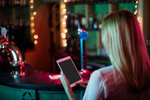 Achteraanzicht van serveerster met behulp van een digitale tablet