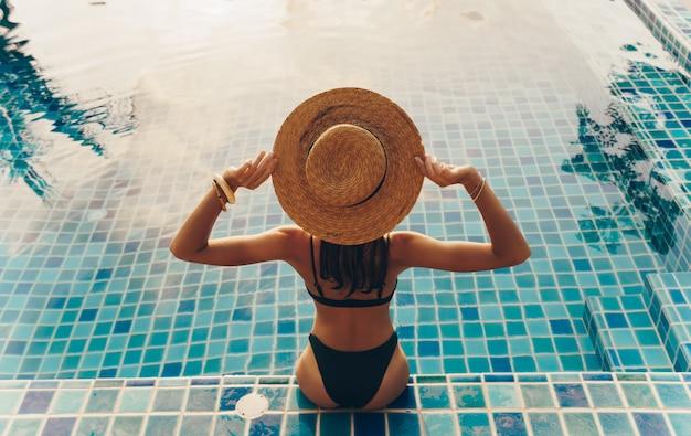 Achteraanzicht van sierlijke vrouw in zwembroek en hoed zitten bij het zwembad