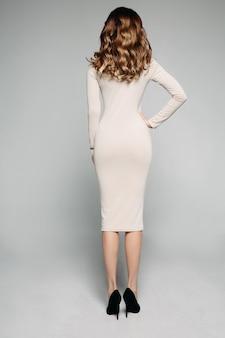 Achteraanzicht van slanke brunette met golvend haar, gekleed in ivoor casual kleding en hakken.