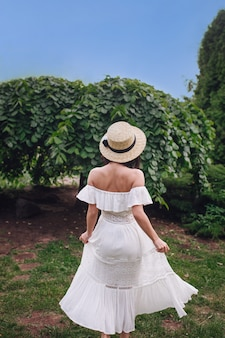 Achteraanzicht van slanke jonge vrouw in strooien hoed en witte jurk