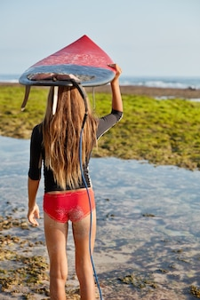 Achteraanzicht van slanke vrouw in rode bikini, heeft lang haar, houdt surfplank boven het hoofd