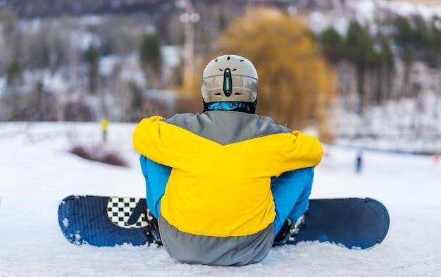 Achteraanzicht van snowboarder zittend op besneeuwde berg