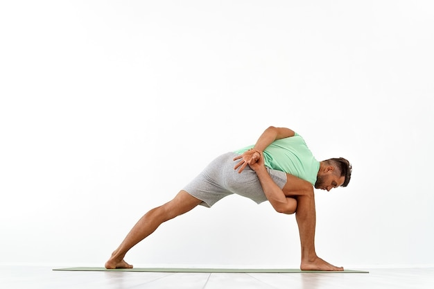 Achteraanzicht van sportieve man die yoga beoefent in yogales die zich uitstrekt terug