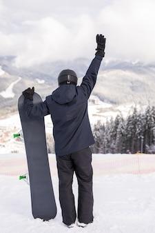 Achteraanzicht van sportman met snowboard kijken naar de natuur met hand omhoog