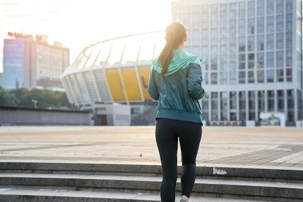 Achteraanzicht van sportvrouw die 's ochtends in de stad op de trap loopt. gezond levensstijlconcept