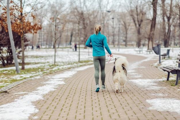 Achteraanzicht van sportvrouw die samen met haar hond in het park loopt bij sneeuwweer. winterfitness, huisdieren, vriendschap, honden