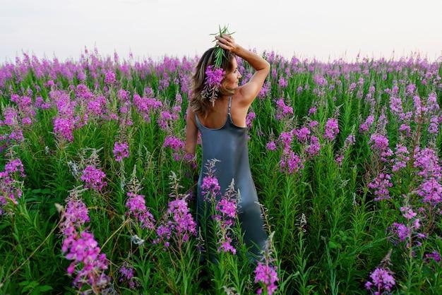 Achteraanzicht van staande jonge blonde vrouw in grijze jurk en met een bos bloemen op wilgenroosje weide