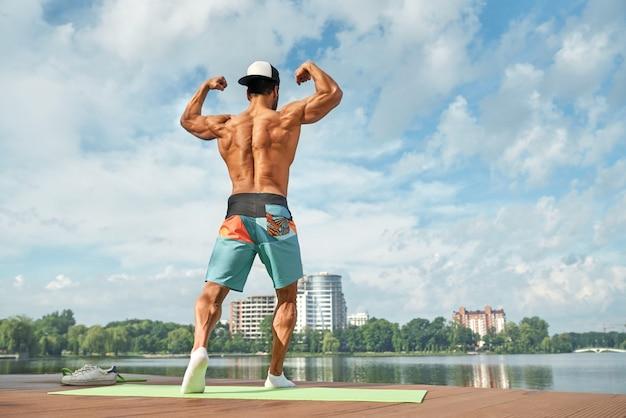 Achteraanzicht van sterker mannetje met blote borst in pose.