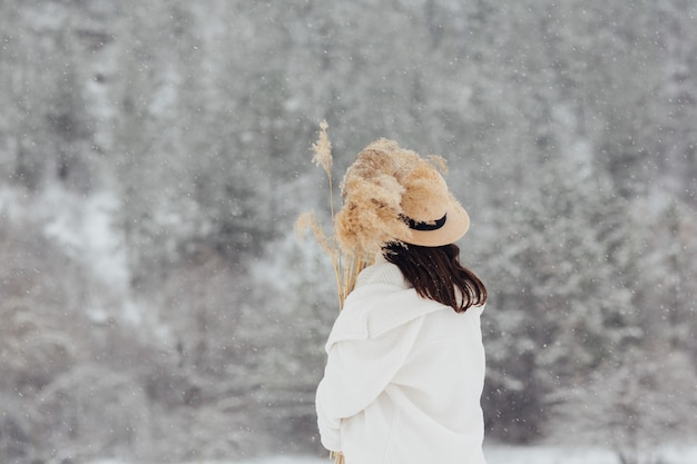 Achteraanzicht van stijlvol meisje met hoed met het boeket van droge riet buiten in de besneeuwde winter.