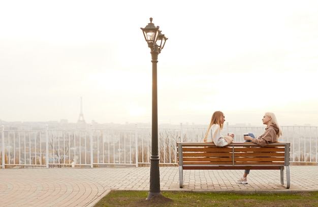 Achteraanzicht van stijlvolle jonge vriendinnen in warme kleren afhaalmaaltijden koffie drinken en vriendelijk chatten, zittend op een bankje tegen wazig stadsgezicht in koude herfstdag