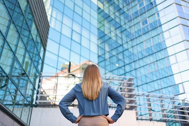 Achteraanzicht van succesvolle manager kijken naar zakelijke gebouw van de moderne stad.