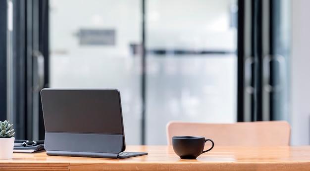 Achteraanzicht van tablet met magisch toetsenbord en kopje koffie op houten tafel.