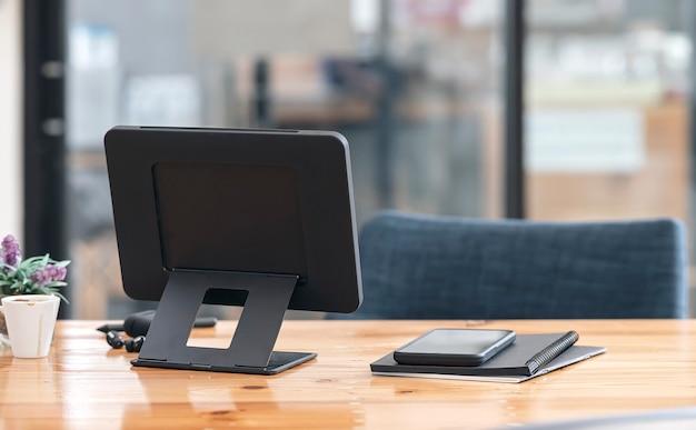 Achteraanzicht van tablet met standaardhouder op houten tafel in moderne kantoorruimte