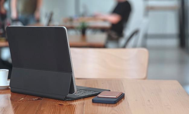 Achteraanzicht van tablet met toetsenbord en smartphone op houten tafel in café.