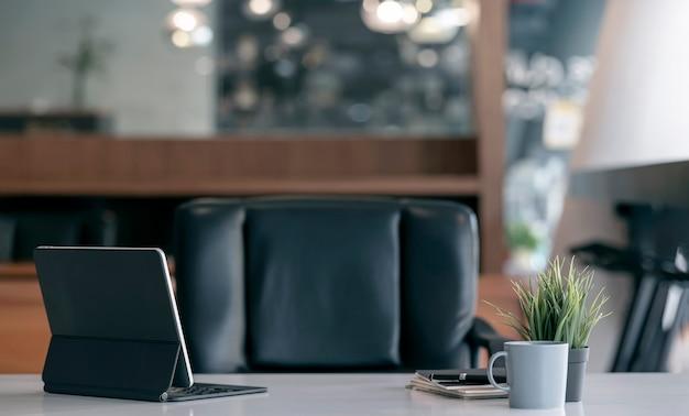 Achteraanzicht van tablet met toetsenbord op tafel in donkere kantoorruimte.