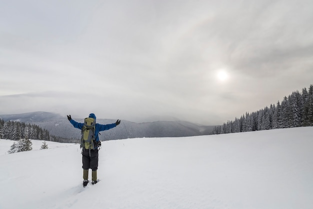 Achteraanzicht van toeristische wandelaar in warme kleding met rugzak staande met opgeheven armen op clearing bedekt met sneeuw op vuren bos berg en bewolkte hemel kopie ruimte achtergrond.